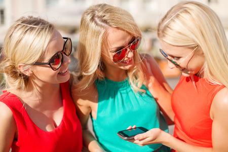 despedida de soltera: vacaciones y el turismo, moderno concepto de tecnología - hermosas chicas rubias con los teléfonos inteligentes en la ciudad