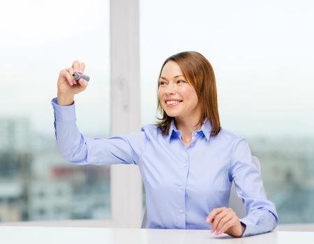 office, business, technology concept - businesswoman writing something in the air with marker photo