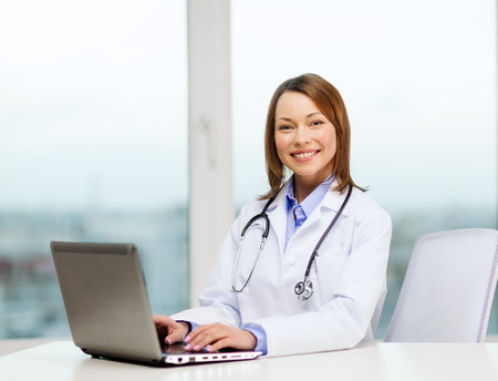 medicine and healthcare concept - busy doctor with laptop computer photo