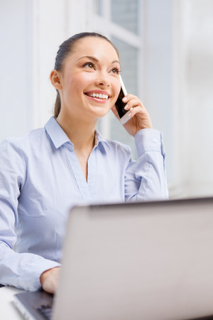 office, business and technology concept - smiling businesswoman with laptop computer and smartphone photo