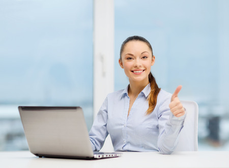 business and technology concept - businesswoman with laptop in office showing thumbs up photo
