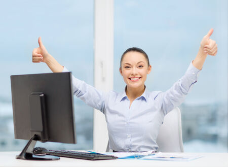 business, internet, office and technology concept - smiling businesswoman with computer and paper showing thumbs up photo