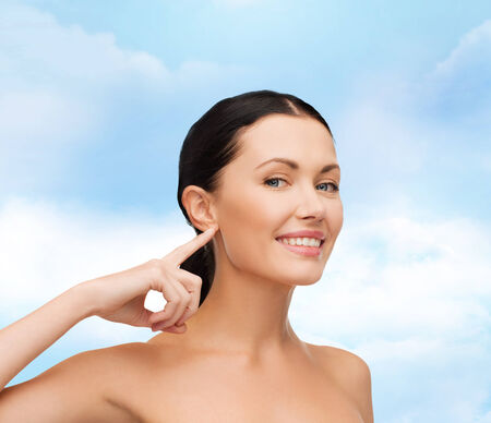 health, spa and beauty concept - clean face of beautiful young woman pointing to her ear photo