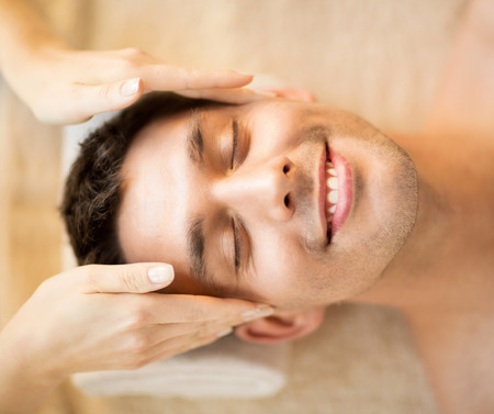 healthcare, spa and beauty concept - man is getting massage at in spa salon photo