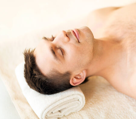 healthcare, spa and beauty concept - close up of man face in spa salon photo