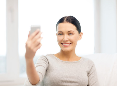 home, technology, photography and internet concept - woman taking picture of herself with smartphone camera photo