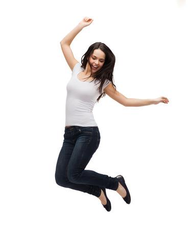 白い空白の t シャツのジャンプで 10 代の少女の笑みを浮かべて - 活動と幸福の概念
