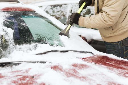transportation, winter and vehicle concept - closeup of man scraping ice from car windshield with brush photo