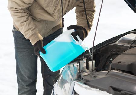 交通機関、冬および車両コンセプト - フロント ガラス水槽に不凍剤を注いで男のクローズ アップ
