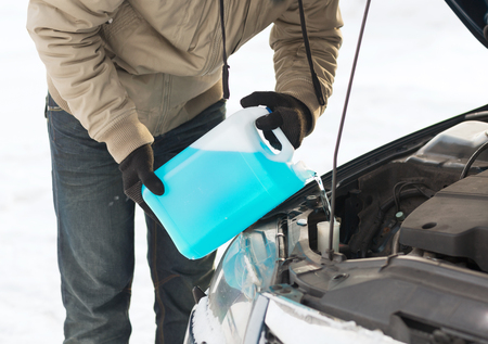 transportation, winter and vehicle concept - closeup of man pouring antifreeze into windscreen water tank photo