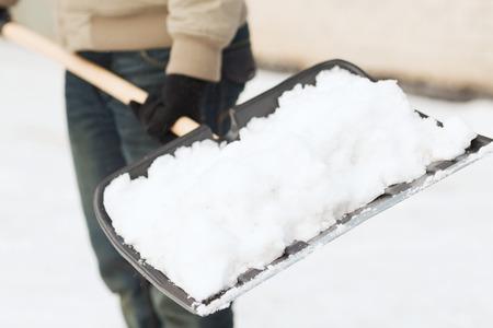 winter en schoonmaken concept - close-up van man sneeuwschuiven van oprit Stockfoto