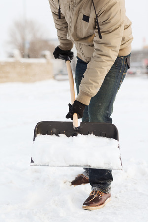 brooming: winter and cleaning concept - closeup of man shoveling snow from driveway