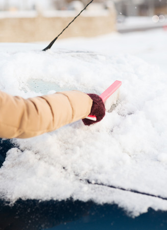 transportation, winter and vehicle concept - closeup woman cleaning snow from car back window with brush photo
