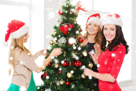 decorating christmas tree: christmas, x-mas, winter, happiness concept - three smiling women in santa helper hats decorating a christmas tree