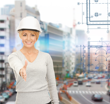 building contractor: building, developing, construction and architecture concept - female contractor in helmet ready for handshake