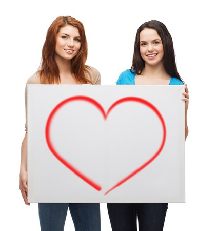 advertisement, love and people concept - smiling young girls with blank white board photo