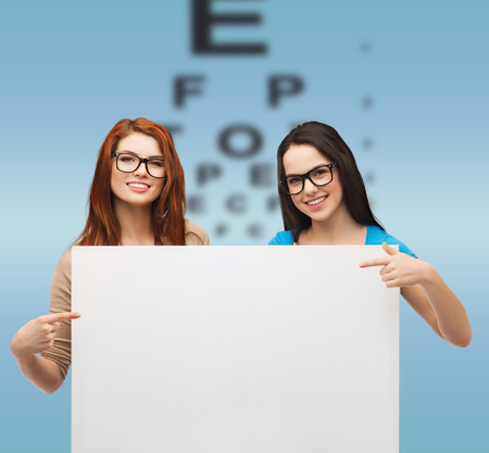 vision, health, advertisement and people concept - two smiling girls wearing eyeglasses pointing fingers to white blank board photo