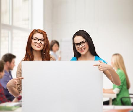 cheque en blanco: visión, salud, publicidad y concepto de la gente - dos niñas sonrientes que usan anteojos que señalan los dedos a la tarjeta en blanco blanco Foto de archivo