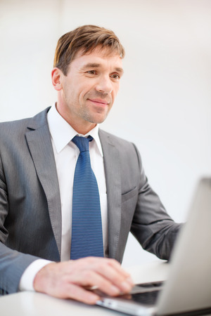 business, internet, technology and office concept - smiling businessman with laptop computer in office photo