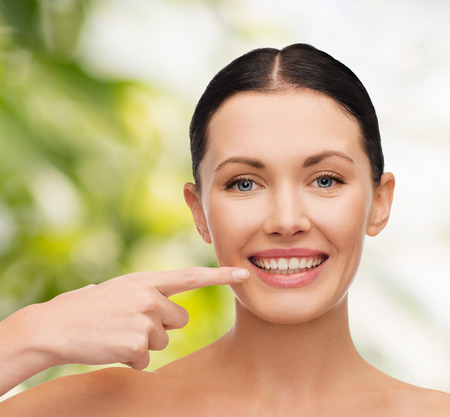 health, spa and beauty concept - clean face of beautiful young woman pointing to her mouth photo