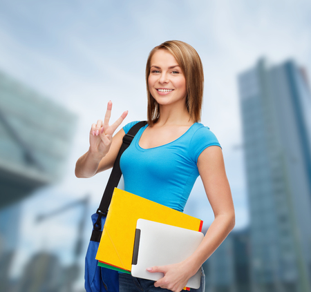education, technology, gesture and people concept - smiling female student with bag, tablet pc computer and folders showing victory gesture photo