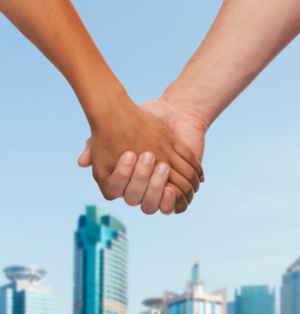 lovers holding hands: love and relationships concept - closeup of woman and man holding hands