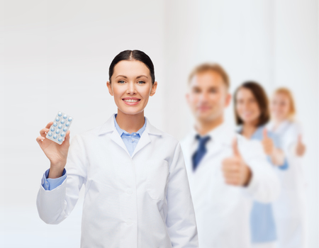 birth control: healthcare, medicine and pharmacy concept - smiling female doctor and with pills