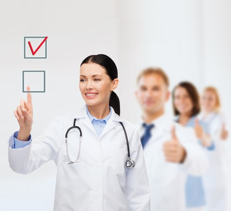 pointing finger up: healthcare, medicine and technology concept - smiling female doctor pointing to checkbox Stock Photo