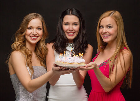 three wishes: celebration, food, friends, bachelorette party and birthday concept - three smiling women holding cake with candles Stock Photo