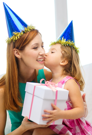 thanking: family, children, celebration, holidays, birthday and happy people concept - happy mother and daughter in blue party hats with gift box Stock Photo