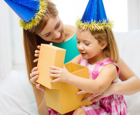 family, children, celebration, holidays, birthday and happy people concept - happy mother and daughter in blue hats with gift box photo