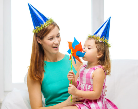 family, children, celebration and happy people concept - happy mother and daughter in blue hats with pinwheel photo