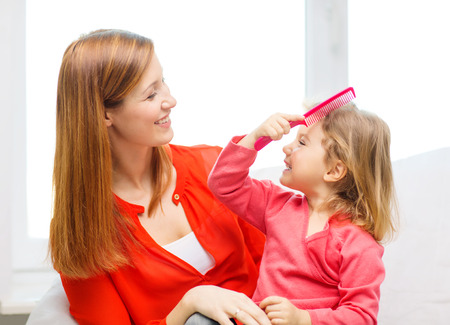 comb: family, children and happy people concept - happy mother and daughter with pink comb