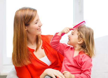 peine: la familia, los niños y la gente feliz concepto - feliz madre e hija con el peine rosa