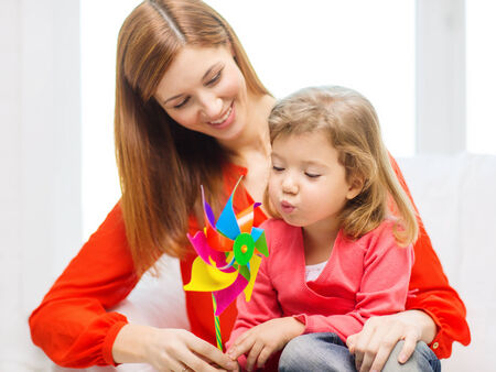 family, children, ecology and happy people concept - happy mother and daughter with pinwheel toy photo