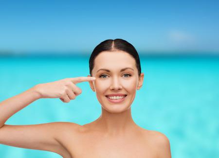 ojos hermosos: la salud, el spa y el concepto de belleza - la cara limpia de la hermosa joven apuntando a su ojo Foto de archivo