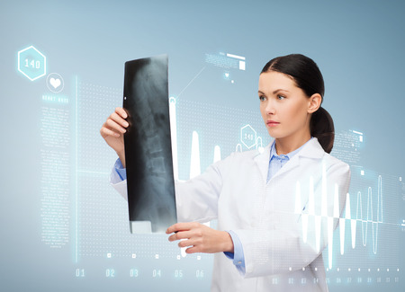 radiology: healthcare, medicine and radiology concept - serious female doctor looking at x-ray