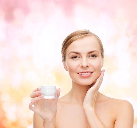aseo personal: cosméticos, salud y el concepto de belleza - mujer hermosa que aplica la crema en su piel