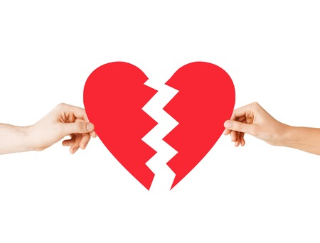 love and relationship problems concept - male and female hands holding two parts of broken heart Stock Photo