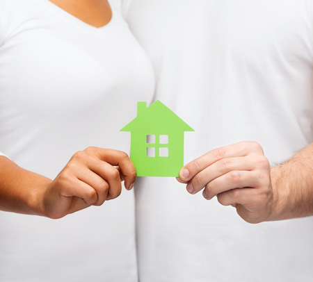 home protection: real estate, family and eco concept - closeup picture of couple hands holding green house