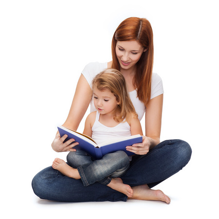 parenting: childhood, parenting and relationship concept - happy mother with adorable little girl reading book