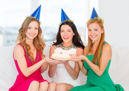 despedida de soltera: celebración, comida, amigos, despedida de soltera, cumpleaños concepto - tres mujeres sonrientes que llevan los sombreros azules sosteniendo el pastel con velas Foto de archivo