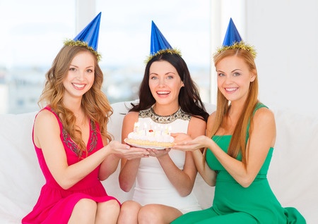 three presents: celebration, food, friends, bachelorette party, birthday concept - three smiling women wearing blue hats holding cake with candles