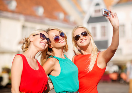 holidays, tourism and modern technology concept - three beautiful girls taking picture with digital camera in the city photo