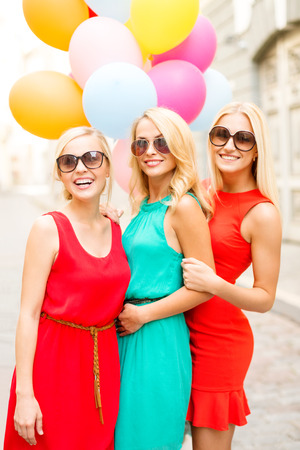 fancy dress party: holidays and tourism, friends, hen party, blonde girls concept - three beautiful women with colorful balloons in the city