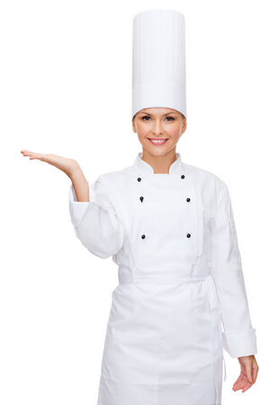 culinary skills: cooking, advertisement and food concept - smiling female chef holding something on palm of hand Stock Photo