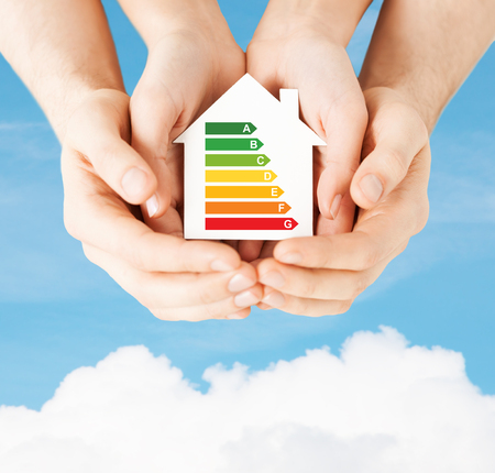save electricity: energy saving, real estate and family home concept - closeup of couple hands holding white paper house with energy efficiency rating Stock Photo