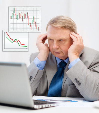 business, technology and office concept - upset older\ businessman with laptop and charts in office