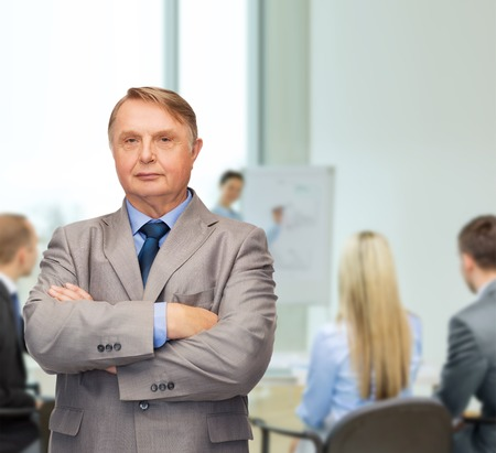 business, office and education concept - serious buisnessman or teacher in suit at office photo