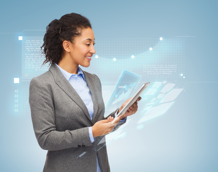 business, internet and technology concept - smiling african-american woman looking at tablet pc computer photo